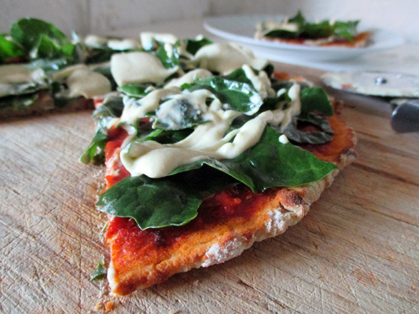 vegan gluten-free yeast-free pizza with silverbeet chard topping and cashew cheese sauce